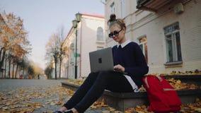 Tonårigt flickasammanträde för nätt hipster på en trottoar på höststadsgatan och arbetebärbar datordatoren Använda för skolflicka lager videofilmer