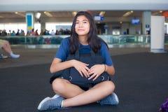 Tonårigt flickasammanträde på golv på hållande bagage för flygplatsterminal Arkivbild