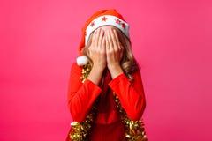 Tonårigt i röd hatt för jultomten` s och med glitter på hennes hals, stänger henne arkivbild