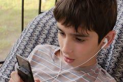 Tonårigt lyssnar musik till och med headphon Royaltyfria Bilder