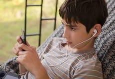 Tonårigt lyssnar musik till och med headphon Fotografering för Bildbyråer