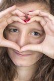 Tonårigt med händer i hjärtaform Fotografering för Bildbyråer