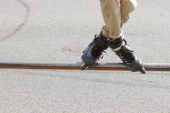 Tonårigt med rullskridskor som utför ett jippo på en halv rörramp Arkivbilder