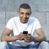 Tonårigt med smartphonen Arkivbild