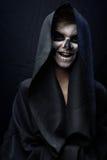 Tonårigt med smink av skallen i svart kappa skrattar royaltyfri foto