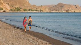 Tonårigt och kvinna som promenerar stranden med handdukar som slås in runt om th arkivbilder