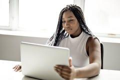 Tonårigt på skrivbordet i hennes kontor med bärbara datorn arkivfoton