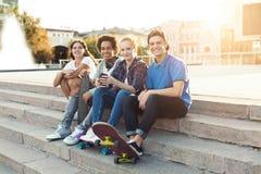 Tonårigt sitta för vänföretag som är utomhus- och att spendera sommar tillsammans arkivbild