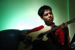 Tonårigt spela en akustisk klassisk gitarr Fotografering för Bildbyråer