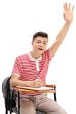 Tonårigt studentsammanträde i en stol och lyfta hans hand Arkivfoton