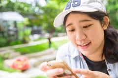 Tonårigt tyck om det användande försiktiga leendet för smartphonen royaltyfri bild