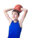 Tonåring i en blå t-skjorta med en orange boll för basket ov Royaltyfria Bilder