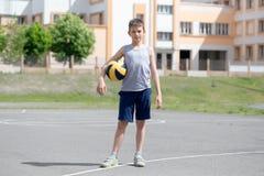 Tonåring i en T-tröja och kortslutningar som spelar med en boll Fotografering för Bildbyråer