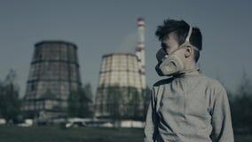 Tonåring i mounthmaskering Pojke i gasmaskrespirator mot den industriella tagna closeupen för röka rör f?rorening f?r fabrik f?r  arkivfilmer