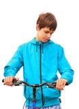 Tonåring med cykeln på vit arkivfoton