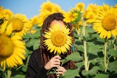 Tonåring med dreadlocks som döljer i sommarmorgonen i ett fält med solrosor royaltyfria bilder