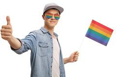 Tonåring med en regnbågeflagga och exponeringsglas som gör en tumme upp gestu Arkivfoton