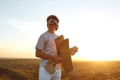 Tonåring med leksakflygplanet på naturen på solnedgången royaltyfria foton