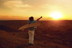 Tonåring med leksakflygplanet på naturen på solnedgången royaltyfri foto