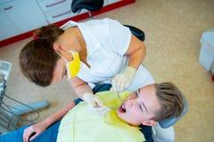 Tonåring på en kvinnlig kirurgi för tandläkare` s royaltyfria foton