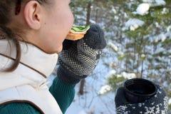 Tonåring som äter smörgåsen i vinterskog arkivfoton