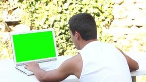 Tonåring som använder datoren i trädgårds- sommartid arkivfilmer
