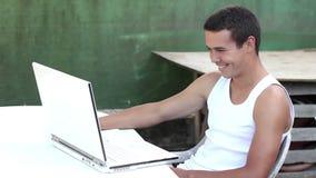 Tonåring som använder datoren i trädgårds- sommartid stock video