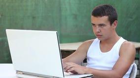 Tonåring som använder datoren i trädgårds- sommartid lager videofilmer