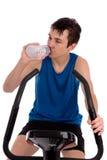 Tonåring som använder motionscykelkonditionidrottshall Arkivfoto