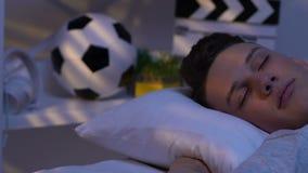 Tonåring som djupt sover i säng, bekväm kudde och ortopedisk madrass lager videofilmer