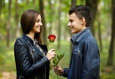 Tonåring som ger en blomma till hans flickvän royaltyfria bilder