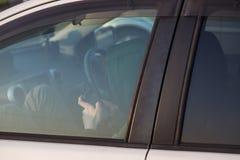 Tonåring som kontrollerar den smarta telefonen, medan sitta i bil arkivfoton
