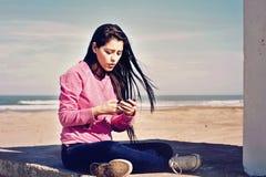Tonåring som läser en text i hennes cell Arkivbilder