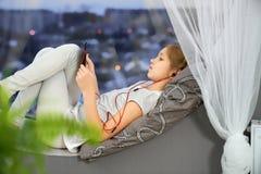 Tonåring som lyssnar till musik som ligger på rund änkafönsterbräda fotografering för bildbyråer
