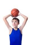 Tonåring som rymmer en boll för basket över hans huvud Isolerad nolla Arkivbild