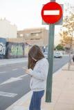 Tonåring som ser mobilen, innan att korsa gatan Royaltyfri Foto