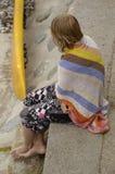 Tonåring som slås in i handduk på stranden   arkivfoton