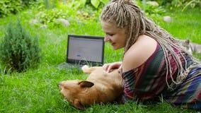 Tonåring som spelar med en hund på gräset HD stock video