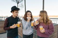 Tonåringar äter gatamat, vänpojken och två flickor på stadsgatan med hamburgare och orange fruktsaft Stadsbakgrund, guld- timme royaltyfri fotografi