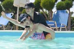 Tonåringar i en simbassäng royaltyfri fotografi