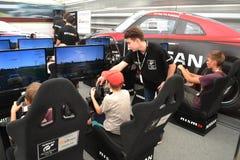 Tonåringar kör simulatorer av den tävlings- leken på det Nismo G-drevet S Fotografering för Bildbyråer