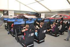Tonåringar kör simulatorer av den tävlings- leken på det Nismo G-drevet S Royaltyfri Foto