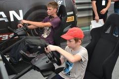 Tonåringar kör simulatorer av den tävlings- leken på det Nismo G-drevet S Arkivfoto
