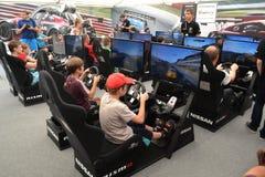Tonåringar kör simulatorer av den tävlings- leken på det Nismo G-drevet S Arkivfoton