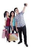 Tonåringar med shoppingpåsar som tar bilder Arkivbild