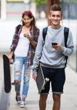Tonåringar med skateboarder utomhus Royaltyfri Bild