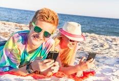 Tonåringar (pojke och flicka) som använder den smarta telefonen och lyssnande musik Arkivbilder