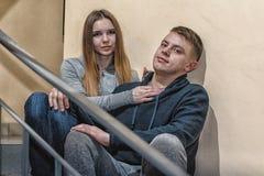 Tonåringar pojkvän och flickvän sitter på momenten i flerbostadshus royaltyfria bilder