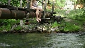 Tonåringar sitter på en smal träbro över en bergflod campa och affärsföretagbegrepp arkivfilmer