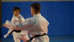 Tonåringar som öva karate och kopplar in i strid genom att använda attack och blockera tekniker på idrottshallen lager videofilmer